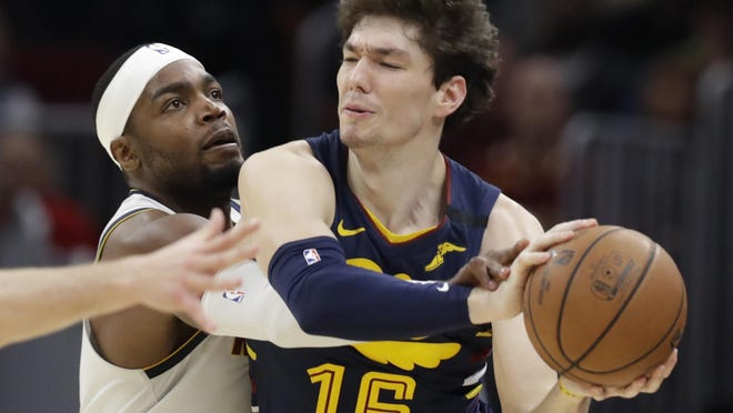 The Denver Nuggets' Paul Millsap, left, tries to knock the ball loose from the Cavaliers' Cedi Osman in the second half of a game in March.