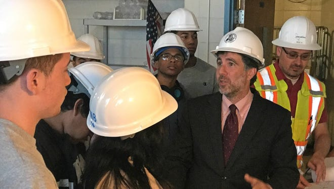 New Brunswick students got real-world engineering experience by visiting the Robeson School construction site. Frank LoDolce, the district's director of Facilities, Design and Construction, is second from right.