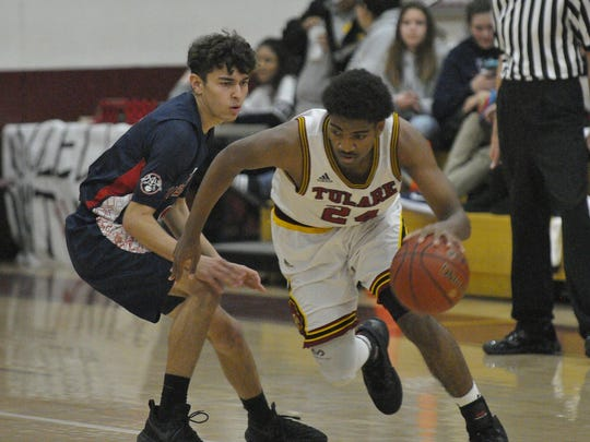 Tulare Union's Jayden Cain dribbles by a Tulare Western defender on Thursday in an East Yosemite League game at Tulare Union.