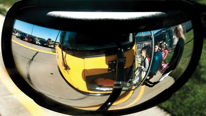 A group of Victor Ornelas Elementary School students are reflected in a school bus mirror as they load the bus to head home after the school day during a past school year. Garden City USD 457 begins classes for select grades on Monday.