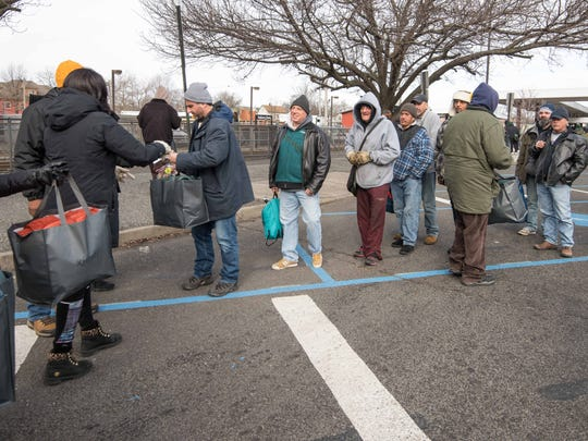 Lisa Savage of Manalapan (far left) distributes goods to the homeless and needy in Asbury Park as part of a Jackson-based outreach project called Meet the Need.