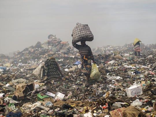 People sift through garbage at the municipal garbage