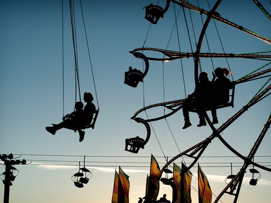Riders in bucket seats of several rides are silhouetted against the setting sun as they enjoy the North Carolina Mountain State Fair on Monday.