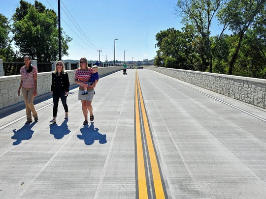 From left, Kimberly Gray, Jennifer Spergl and Mandy Whitson, holding her 2-year-old son Sam, make their way on the new bridge to the opening ceremony of a long-awaited Carothers extension in Franklin, Tenn., Wednesday, Sept. 23, 2015.