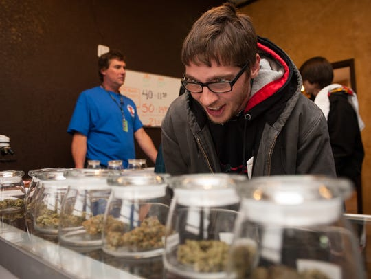 Tyler Williams of Blanchester, Ohio selects marijuana strains to purchase at the 3-D Denver Discrete Dispensary on January 1, 2014 in Denver, Colorado.