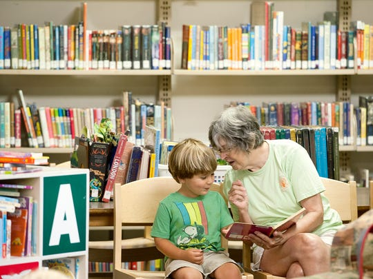Maggie Winn reads a story to her grandson, Wayah Stone, 3, at the East Asheville Library on Wednesday, July 22, 2015. The library is well used and in need of renovation or expansion.