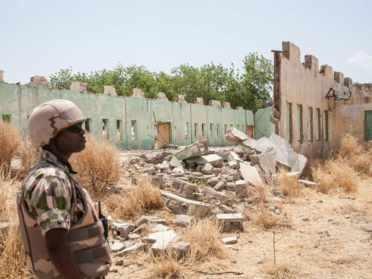 A Nigerian solider stands in front of the remains of