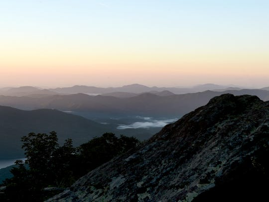 The sun rises over the mountains as seen from Craggy