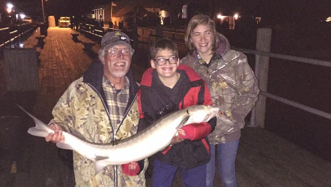 Jim Felgenauer of Sturgeon for Tomorrow holds one of the mighty fish with Sam Pandolfi of Berkley, center. Natalya Rivers Lohrer suggested sturgeon fishing as a bar mitzvah gift Pandolfi would always remember.
