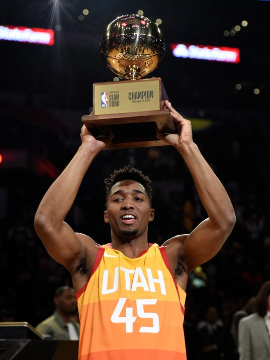Utah Jazz's Donovan Mitchell holds up the trophy after winning the NBA basketball All-Star weekend slam dunk contest Saturday, Feb. 17, 2018, in Los Angeles. (AP Photo/Chris Pizzello)