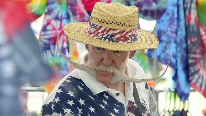 Jake Vivian of Sparks rocked an epic handlebar moustache while looking at tie-dyed items for sale at the park.