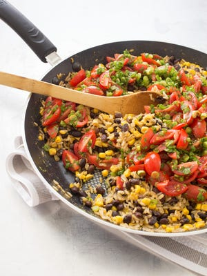 Skillet brown rice with beans, corn and cherry tomato salsa offers a satisfying vegetarian meal.