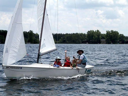 The Siegle family, Ann, Eyrin, Christian and George (left to right), in their sailboat on Lake Lansing.