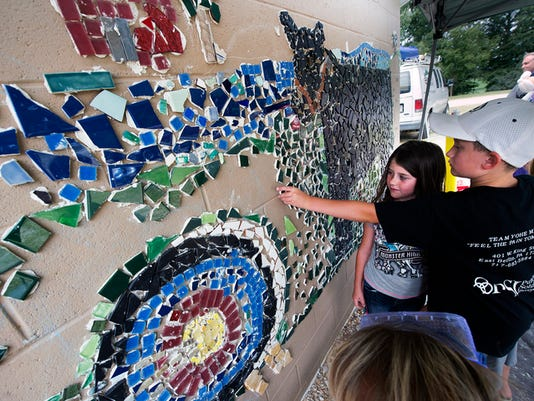 Brynn Yohe, age 6, left, and her brother Bryce, age 8, piece together this year's mural that depicts archery and steer during the York County 4H Fair at the York County 4-H Center Sunday August 9, 2015 in West Manchester Township. The mural that wraps around a block building is added to each year.  Paul Kuehnel - York Daily Record/ Sunday News