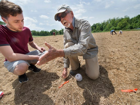 Ben Taylor, a York College student from York, works with Steve Warfel, marking where a trench will be dug at the Camp Security dig site in Springettsbury Township Wednesday May 20, 2015.. Paul Kuehnel - Daily Record/Sunday News
