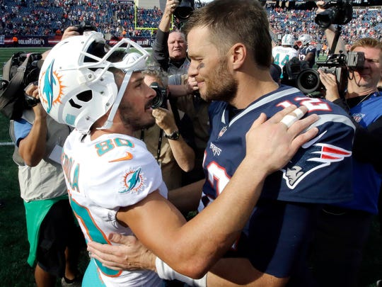 Miami Dolphins wide receiver Danny Amendola, left, and New England Patriots quarterback Tom Brady speak at midfield after an NFL football game, Sunday, Sept. 30, 2018, in Foxborough, Mass. (AP Photo/Steven Senne)