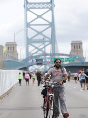 """Gabriel Evans, of Burlington, New Jersey, walks his bike on the Ben Franklin Bridge. Evans rode his bike 17 miles to try and catch a glimpse of Pope Francis. """"I'm not Catholic, but he's a leader,"""" Evans said. """"I'm gonna cross my fingers and hope I get close enough."""""""