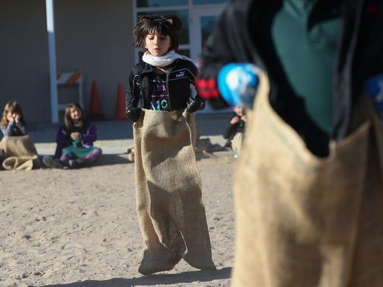 Soraya Kamalie, 6, jumps in a gunny sack during a race