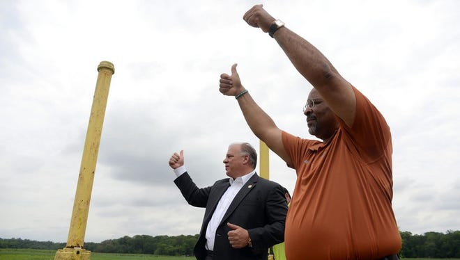 Bridgeton mayor Albert Kelly (right) and NJ State Senate President Steve Sweeney, give thumbs-up to spectators after they close the last gate to allow Sunset Lake and the raceway to refill during an event to mark the official reopening of Sunset Lake, Monday, Jun. 1, 2015 in Bridgeton.  Staff Photo/Sean M. Fitzgerald