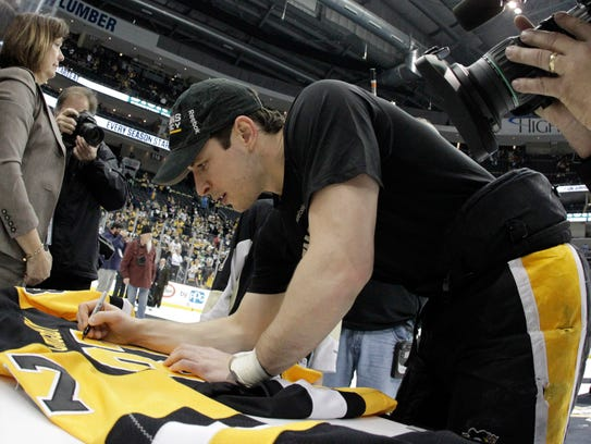 Pittsburgh Penguins center Sidney Crosby (87) signs