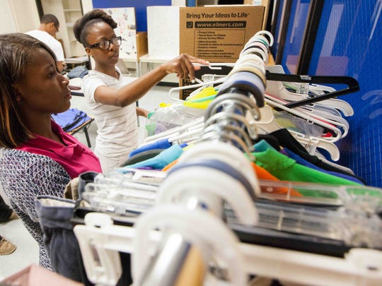 Tamika Lee (second from left), a site director with Community in Schools at A.I. duPont High School, works with freshman Talijah Archie, 16, as they organize a room full of donated clothes from school faculty members.