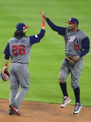 United States outfielder Adam Jones and teammate Brandon Crawford celebrate after defeating Japan in the semifinal of the World Baseball Classic at Dodger Stadium.