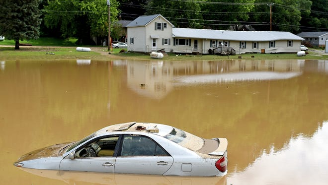 A car is submerged due to flood water near the bridge over Brewery Creek following Friday night storms in Cassville.