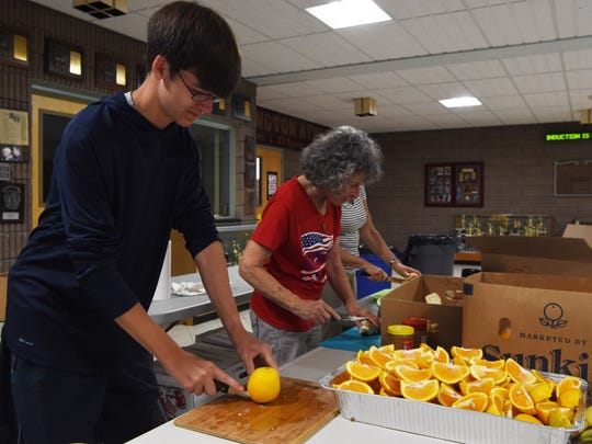 Dan Eastman, left, 16, of Lagrangeville, slices up oranges at Arlington High School before the 2016 Dutchess County Classic. Eastman also ran the 5K portion of the Classic.