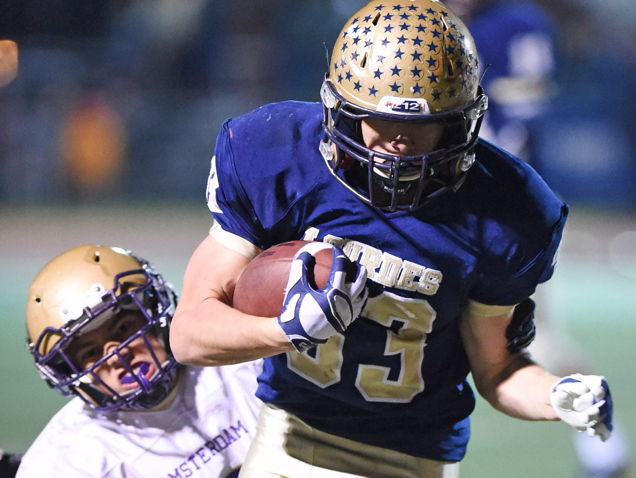 Lourdes' Joe Scaglione carries the ball as Amsterdam's Adel Rosario grabs a hold of him during the Class A semi final at Dietz Stadium.