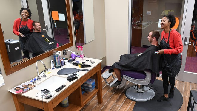 Haircare specialist Tyler Barton laughs as she cuts Hunter Renfrow's hair in the barber shop inside Clemson's Allen N. Reeves Football Complex on Tuesday, September 29, 2017.