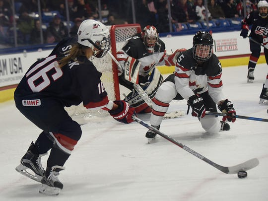 Team USA's Kelli Stack (16) looks before making a pass