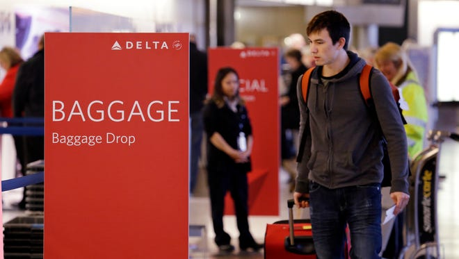 This file photo from March 24, 2015, shows fliers within view of the baggage drop area for Delta airlines at Seattle-Tacoma International Airport.