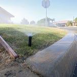 A misaligned sprinkler sends water into a gutter in La Quinta in 2015.