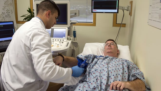 Research assistant Gerran Salto, left, prepares patient Jeff Foster for an ultrasound at the Framingham Heart Study Clinic.