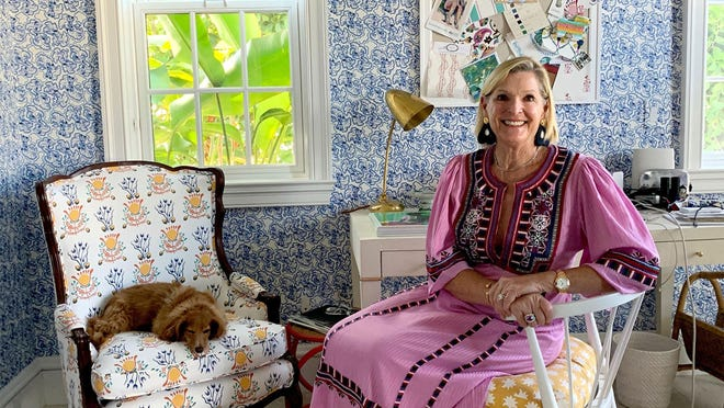 "At her Palm Beach vacation home, designer Mally Skok sits in her office, with its walls covered in her Brimfield pattern. Her Emmie fabric was used for window treatments and the chair upholstery. ""I wanted my office to be a capsule of my design vibe,"" says Skok, whose company, Mally Skok Design, is based in Boston."