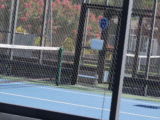 One of the platform tennis courts at Manklin Meadows in Ocean Pines. The cage of metal screens that surrounds each court is used to bounce the ball at different angles during play.