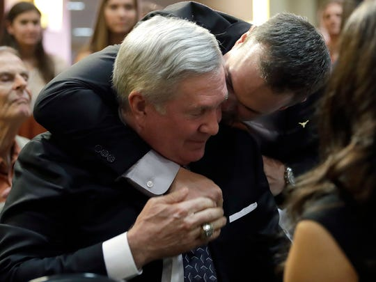 New Texas head NCAA college football coach Tom Herman, right, hugs former Texas head coach Mack Brown, left, before a news conference where Herman was introduced, Sunday, Nov. 27, 2016, in Austin. (AP Photo/Eric Gay)