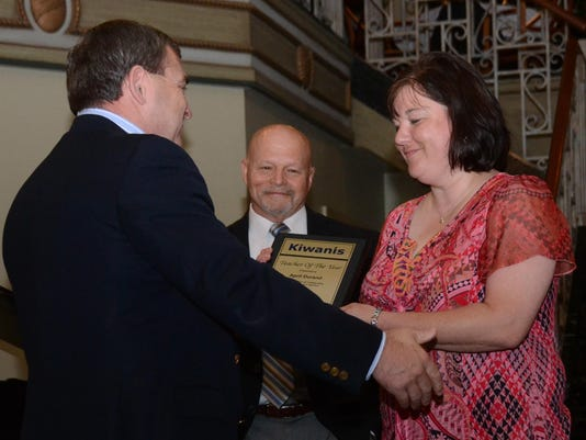 ANI Kiwanis Teacher of Year Kiwanis Club of Alexandria president Barett Byrd (left) hands April Durand a plaque after she was recognized as the Kiwanis Club of Alexandria's Teacher of the Year Thursday, June 18, 2015 during a meeting held at the Diamond Gr