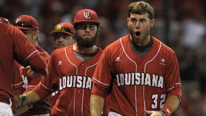 """UL first baseman Chase Compton (32) celebrates with teammates after second baseman Jace Conrad (19) scored off of a single by shortstop Blake Trahan (4)   during the ninth inning of an NCAA Regional baseball game against Mississippi St. at M.L. """"Tigue"""" Moore Field in Lafayette, LA, Monday, June 2, 2014. Paul Kieu, The Advertiser"""