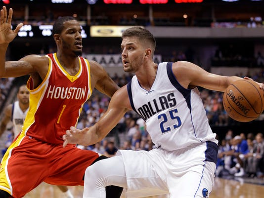 Dallas Mavericks' Chandler Parsons (25) looks for an opening as Houston Rockets' Trevor Ariza (1) defends in the second half of a preseason NBA basketball game, Tuesday, Oct. 7, 2014, in Dallas. The Rockets won 111-108. (AP Photo/Tony Gutierrez)