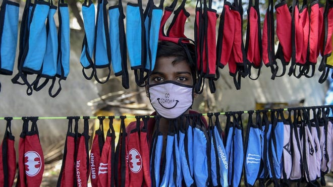 A street vendor poses as he arranges facemasks to sell on the roadside as a preventive measure against the spread of the COVID-19 coronavirus on the outskirts of Hyderabad, India, on June 5, 2020.