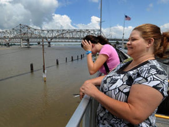 Visitors stand on the floodwall along the Atchafalaya