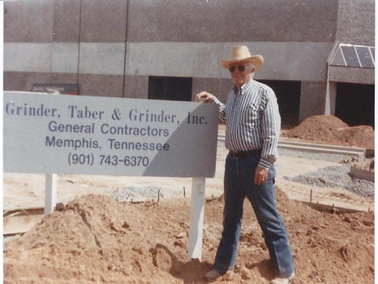 Edward Grinder poses with a sign for his family's Memphis contracting company in July 1986.