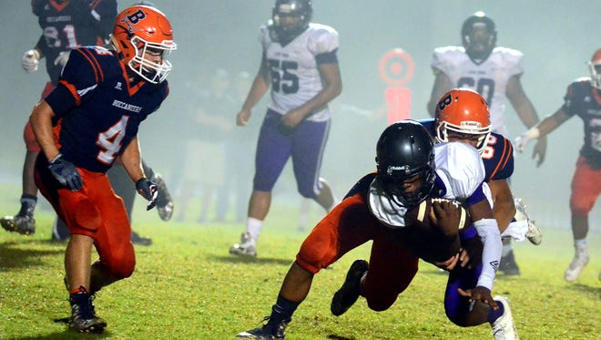 Beech senior Logan Fetzer tackles Cane Ridge senior quarterback D.J. Thorpe as Ty Dean (4) closes in during fourth-quarter action. Cane Ridge defeated the Buccaneers 17-16 on Friday evening.