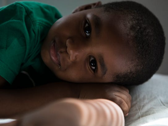 Tylier Drew, 5, lies on his bed at his home in Wilmington.