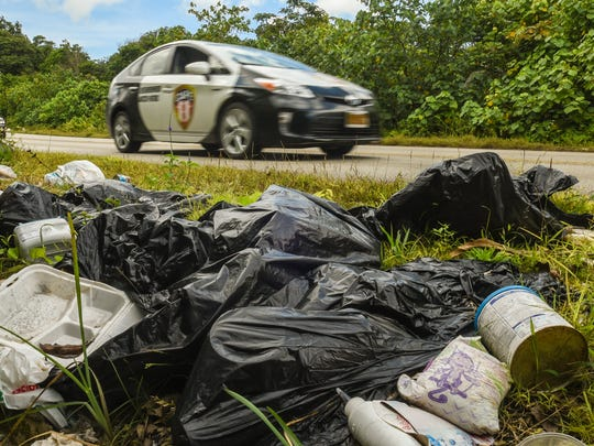 Guam Police Department vehicles drive past bags of