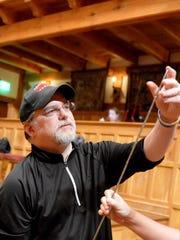 Artistic Director Jim Warren inspects one of the swords