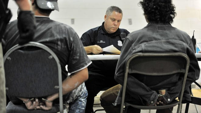 Detroit police officer Brian Ambrous does the paperwork for a vehicle from two men from Sterling Heights at the 12th Precinct in Detroit. The vehicle was impounded after the men were charged for intent to buy drugs.