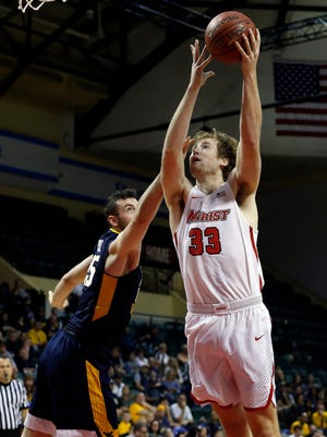 Marist College's Connor McClenaghan shoots over West Virginia's Maciej Bender at HP Field House in Florida in this November 2017 file photo.