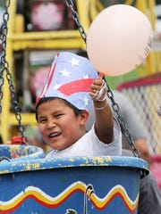 Isaac Nargo, 5, enjoys a carnival ride at the Freedom Days Party in the Park on July 4, 2013, at Brookside Park in Farmington.
